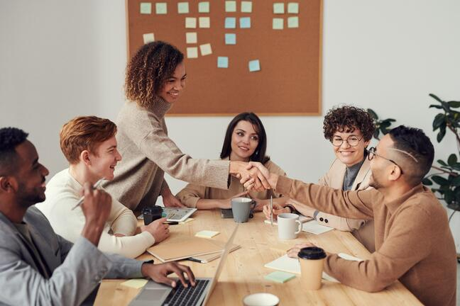People sitting around a table for a meeting, shaking hands