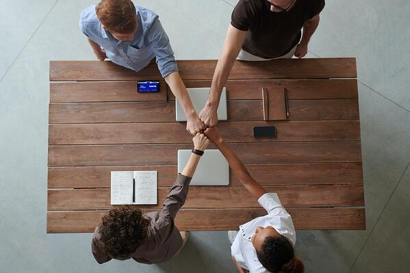 Startup team fistbumping over table