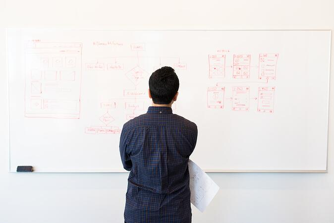 man looking at whiteboard with app design-2