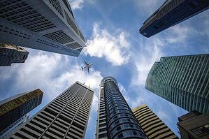 Skyscrapers and a plane below a clear sky